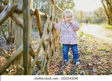 One year old girl standing next to wooden fence in park. Toddler learning how to walk.