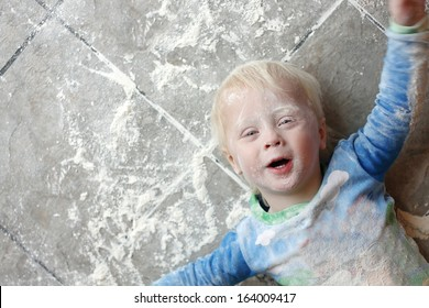 a one year old small child is laying on a very messy kitchen floor, covered in white baking flour.  Room for text, copy space