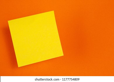 One yellow paper stickers hanging in the air (levitate) on a orange background