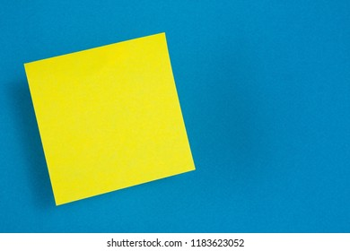 One yellow paper stickers hanging in the air (levitate) on a blue background