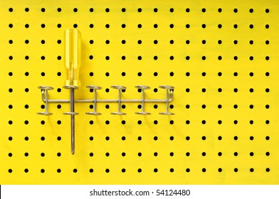 One yellow Phillips screwdriver sits in a rack on a yellow pegboard.