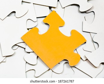 one yellow piece of puzzle on pile of white jigsaw puzzles