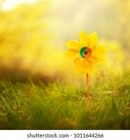 One yellow pinwheel against nature background in sunny summer day.