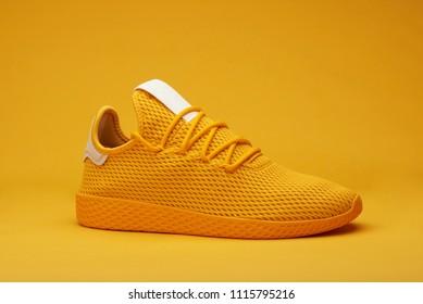 One yellow sport shoe isolated on orange background