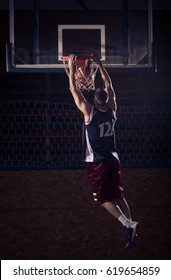 one young adult man, basketball player slam dunk, in air. dark indoors, rear view