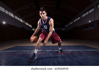 one young adult man, basketball player dribbling ball thought the legs, looking at camera, indoors, dark basketball court