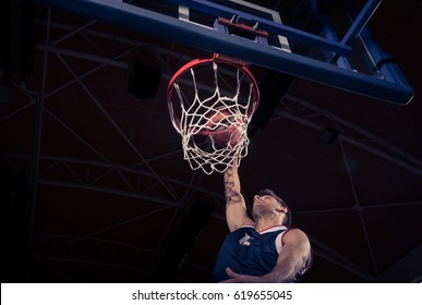 one young adult man, basketball player, one hand, net rim, low angle view, slam dunk, dark indoors.