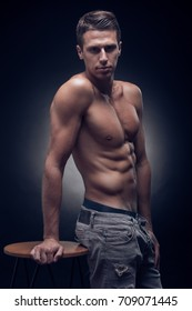 one young adult man, Caucasian, fitness model, muscular body, shirtless, jeans, black background, studio, posing, looking at camera