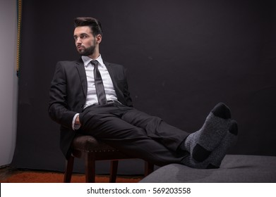 one young adult man handsome sitting chair relaxing socks suit elegant shirt tie pants
