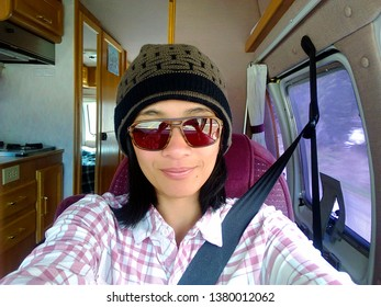 One young adult millennial woman taking a selfie from inside a camper van vehicle on getting away travel vacation holiday journey travel road trip in British Columbia, Canada.