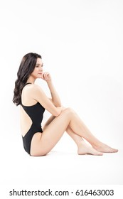 one young adult woman swimsuit sitting, white background, full body shot