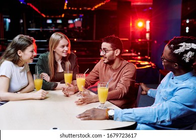 One of young affectionate intercultural friends explaining something while others looking at him by table in leisure center cafe