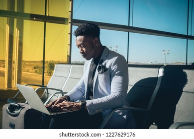 One young and attractive black businessman is seated in the airport terminal working with a laptop, and smiling. He is carrying a suitcase and wearing formal clothes but not a suit.