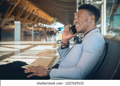 One young and attractive black businessman is seated in the airport terminal near the check-in desks, smiling and talking by telephone. He is wearing formal clothes but not a suit.