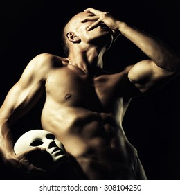 One young bare faceless man with sexual strong muscular attractive body with raised hand and beautiful chest holding one white mask standing on black studio background, square picture