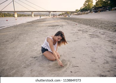 one young beautiful girl, drawing in sand with a stick, sitting in sand. Large beach in background with bridge. Novi Sad, Serbia.