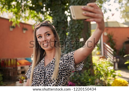 4e2f381360b3 one young beautiful girl taking a snapshot, photographing herself, selfie,  in cafe garden