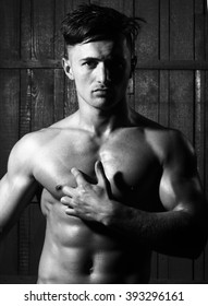 One young beautiful sexy athletic man dark-haired with naked strong chest and perfect abs pectorals muscles and muscular torso looking straight posing on gray wooden background studio, vertical