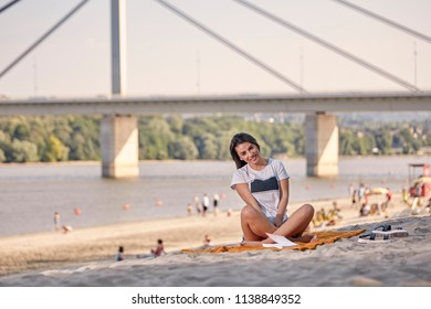 one young beautiful woman smiling, sunny day, reading a book, looking to camera, sitting on blanket, sandy beach. Unrecognizable people in background. Coast, bridge, river in background.
