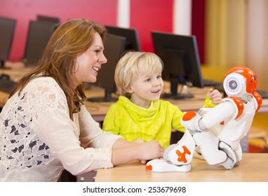 One young boy programming a robot with his science teacher on a primary school