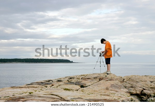 one young boy videographer setting up a tripod and camera to tape the natural surroundings