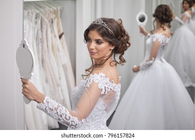 one young bride, looking at self in mirror, bridal salon, wearing gown.
