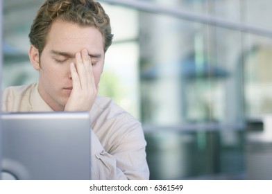 One young business man with head in hands with laptop in front