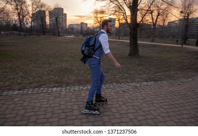 one young businessman, 20-29 years old, ridding inline skates in a park.