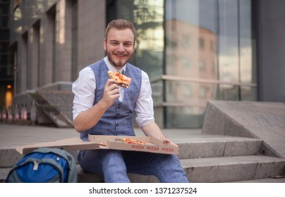 one young businessman, 20-29 years old, eating a pizza slice, looking to camera.