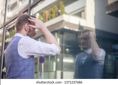 one young businessman, 20-29 years old, setting his hairstyle, touching his head looking at himself in a window mirror.