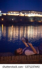 one young businessman, 20-29 years old , laying beside a river and reading a book, night time.