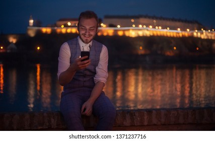 one young businessman, 20-29 years old , sitting near a river, night time,while looking to his phone.