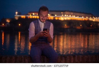 one young businessman, 20-29 years old, sitting near a river, night time,while looking to his phone.