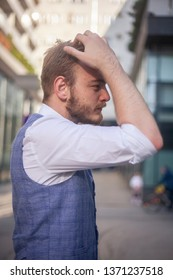 one young businessman, looking to himself, setting his hairstyle. side view.