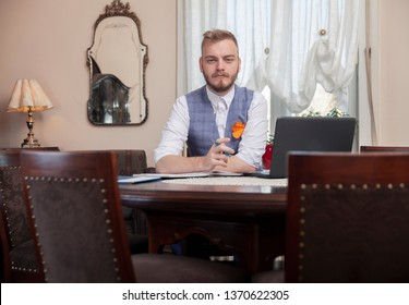one young businessman portrait, looking to camera. sitting in chair in his home interior, antique furniture. On table is laptop and notebook.