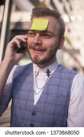one young businessman, talking on a phone, with sticky note attached to his forehead. positive face expression.