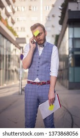 one young businessman talking on a phone, while post-it note is comically attached to his forehead, in a disbelief.