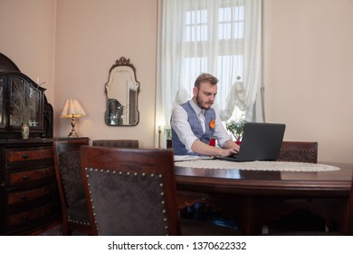 one young businessman working on his laptop, in his apartment room, filled with antique furniture.