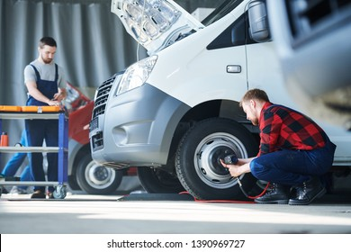 One of young car service professionals fixing wheel detail while his colleague bending over toolbox on background