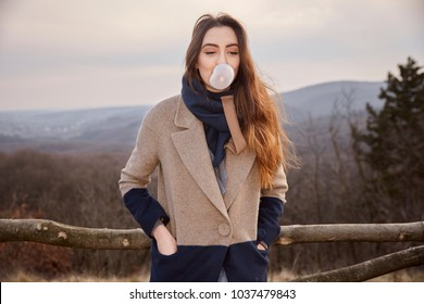 one young cute Caucasian girl, looking away, blowing bubble gum, wearing winter autumn coat, scarf.