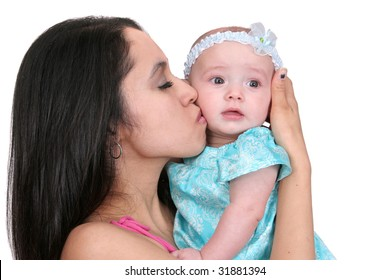 one young dark haired mother in pink kissing her young baby girl child