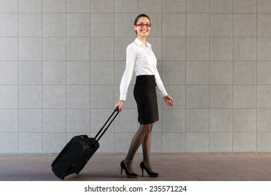 One young elegant woman walking with travel bag