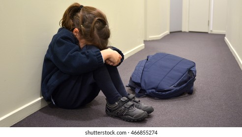 One young elementary school girl (age 5-6)  wearing school uniform and backpack sitting on a corridor floor,  cry in a corridor.Childhood concept. copy space
