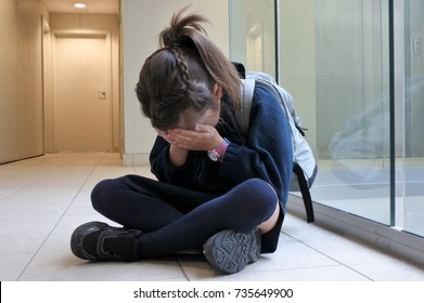 One young elementary school girl wearing school uniform and backpack sitting on a corridor floor crying. Childhood and education concept.