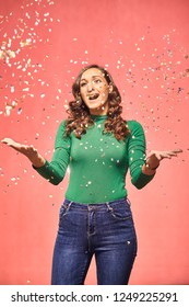 one young excited woman, 20-29 years, confetti falling down, she is excited and shouting with mouth open while her arms are outstretched. shot in studio on pink background
