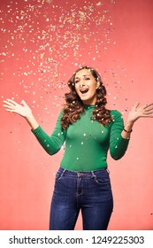 one young excited woman, 20-29 years, confetti falling down, she is excited and shouting with mouth open while her arms are outs outstretched. shot in studio on pink background.