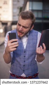 one young furious businessman, holding his phone. upper body shot, wearing suit.