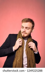 one young gentleman, 20-29 years old, posing with suit and scarf, looking sideways. pink background, studio shot, photo shoot.