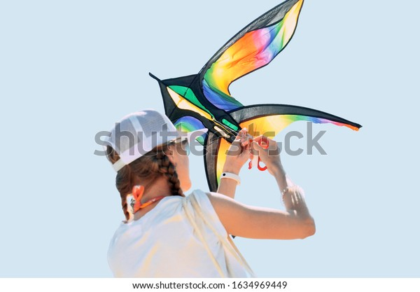 One young girl launches a kite in the sky. Clear background.