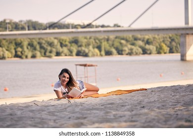 one young girl, relaxing reading a book outdoors, casual clothes, sunny day, laying on blanket, on sandy beach. looking to camera. unrecognizable people in background, river, trees, coast, bridge.